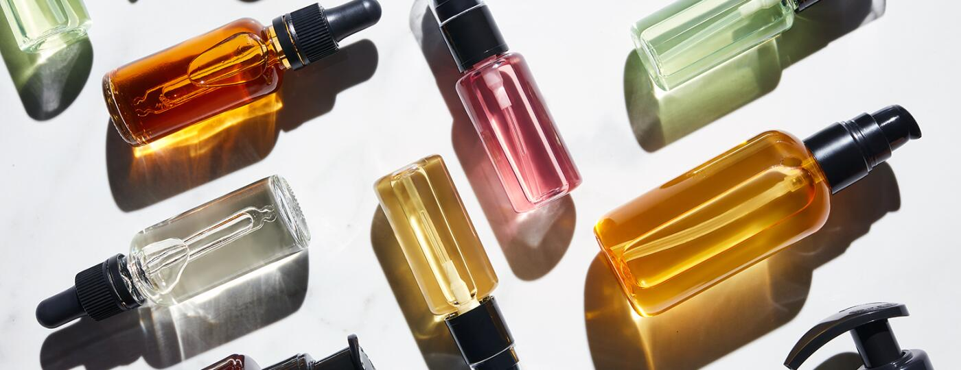 Different Bottles Of Colorful Liquids On White.