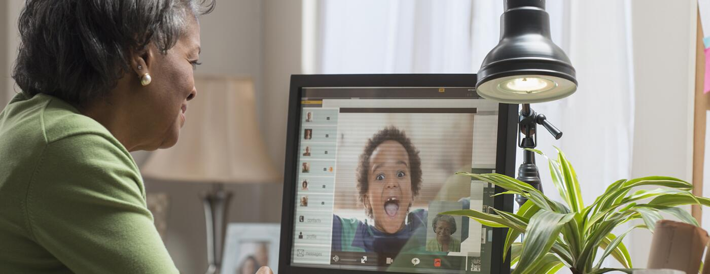 Black woman video conferencing with grandson on computer