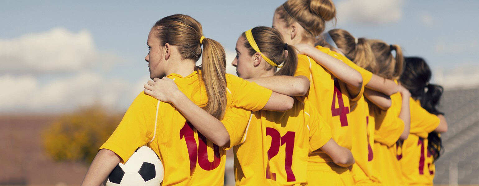 Young girls playing soccer standing on the sidelines arm and arm before the game