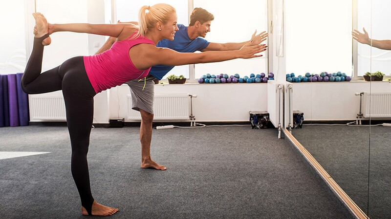 A man and woman doing a leg stretch