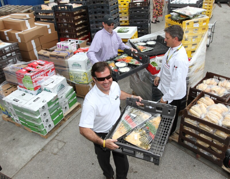 Volunteers collect food from Daytona Speedway Monday.