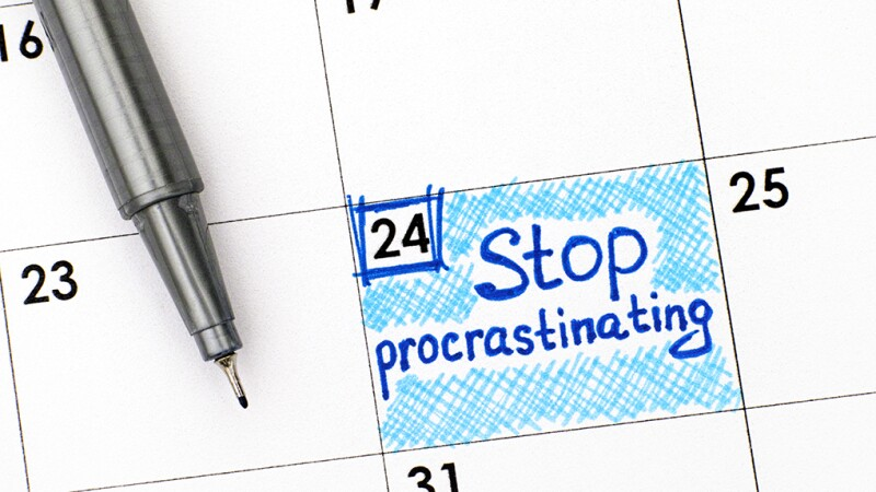"""A close-up view of a calendar with """"Stop procrastinating"""" written on it"""