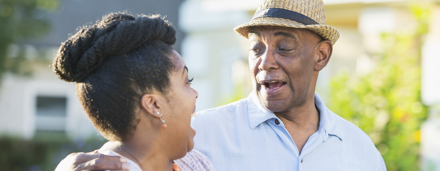 Senior man in front yard with adult daughter