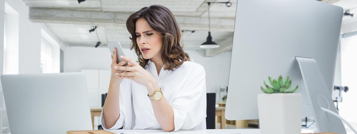 woman at work looking at her phone upset