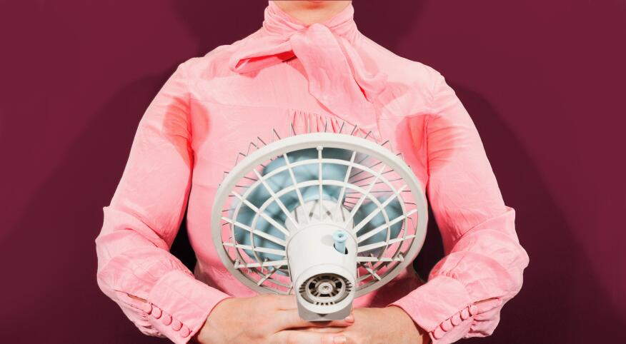 Woman holding a fan with sweat stains