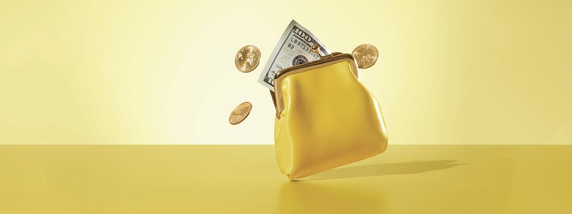 yellow coin purse with money and coins coming out of it