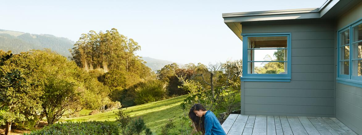 Woman sitting alone on her back porch surrounded by nature