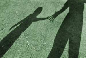 Shadows of adult giving helping hand to child