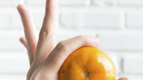 hand holding orange in Okay gesture