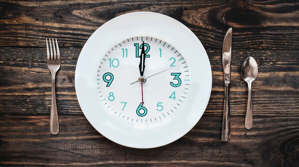 A clock in the form of a plate on a rustic wooden table