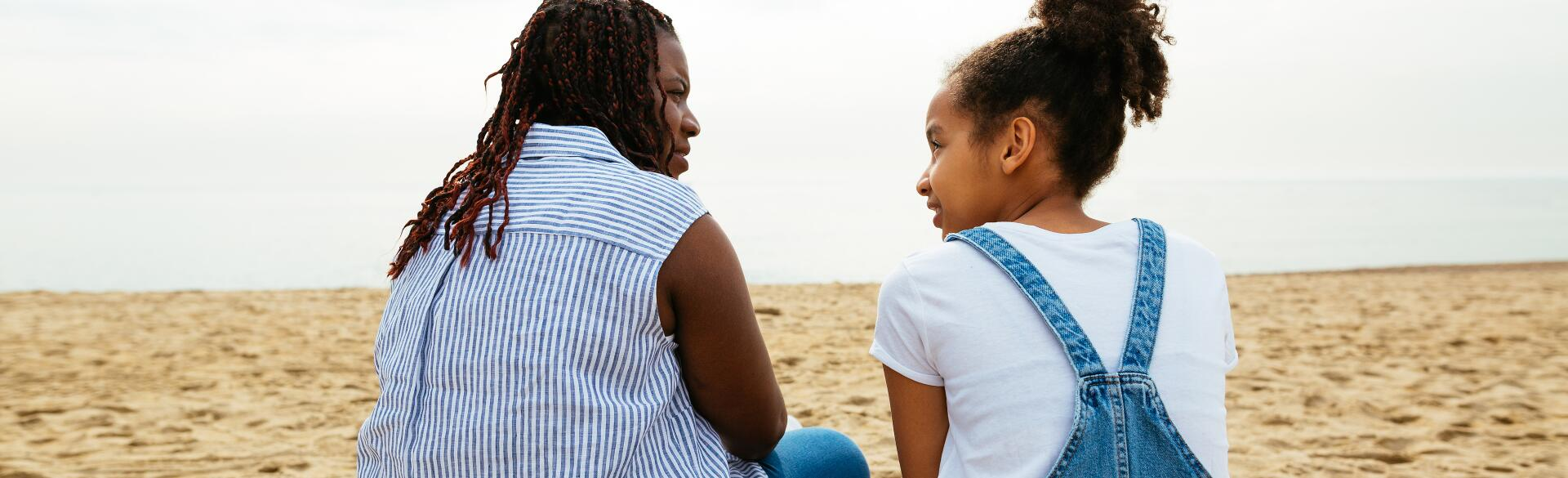 A stepmother sits with her stepdaughter on the beach.