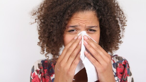 African-American woman sneezing into tissue