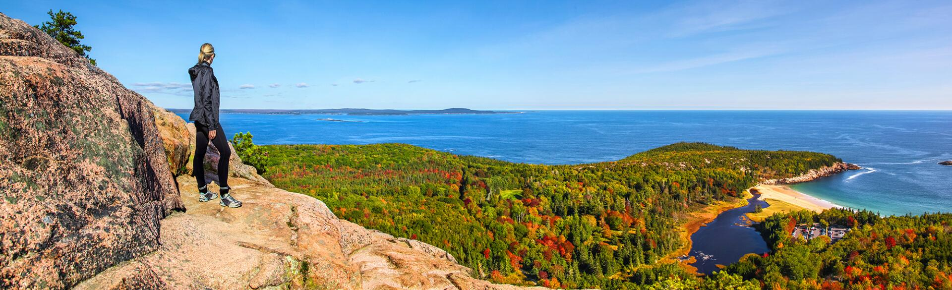 Hiker enjoying the panoramic view from the top of Beehive Trail in Acadia National Park