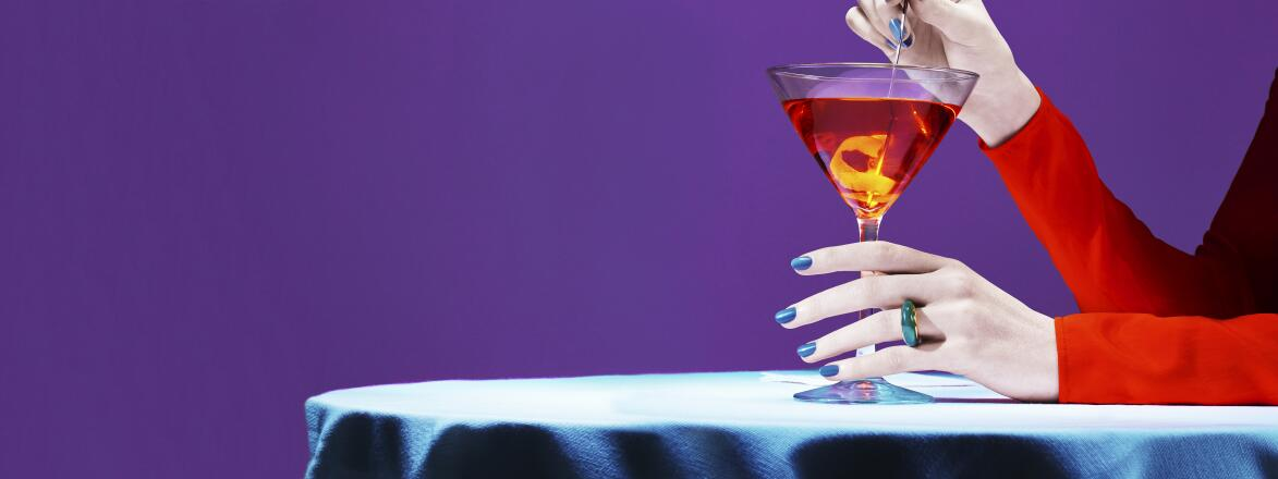 woman's hands holding a martini glass