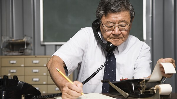 A man using a phone and adding machine while writing all at the same time