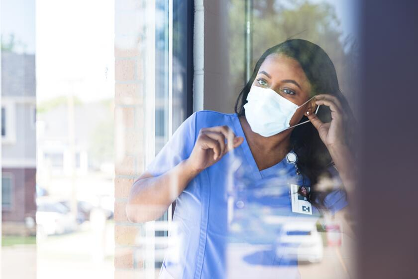 woman_wearing_mask_working_as_nurse_GettyImages-1254704714