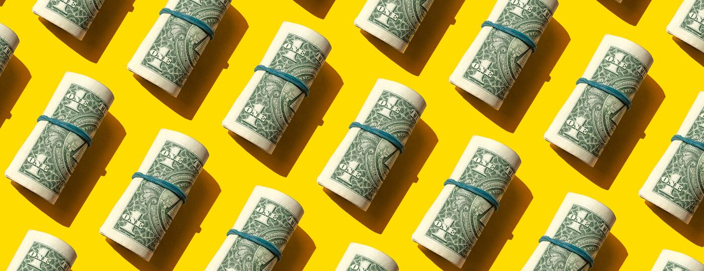 image_of_rolled_dollar_bills_on_background_GettyImages-1270998711_v2_1800