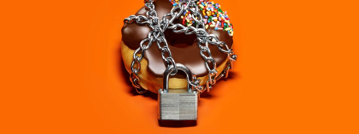 A chocolate frosted donut on an orange background with a chain and lock around it.