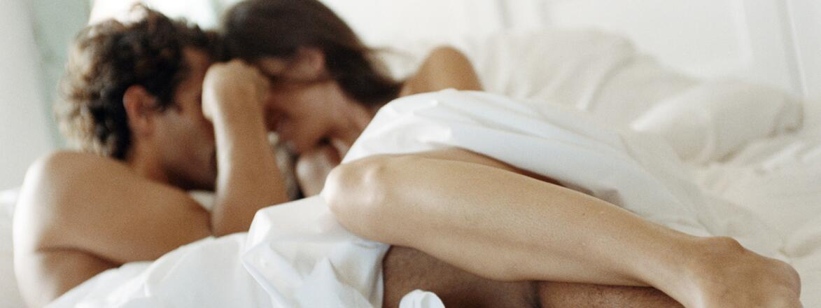 man and women in bed under the sheets getting intimate
