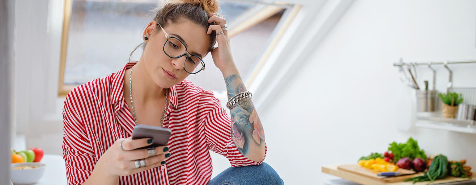 woman who is upset looking at phone after seeing her ex husband unfriended her on facebook