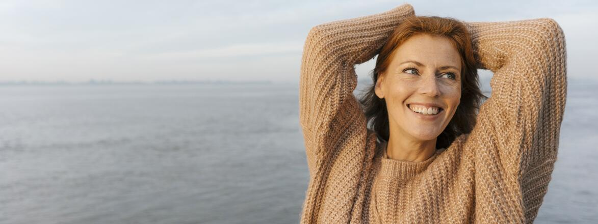 happy woman in her 40s by the water in a sweater