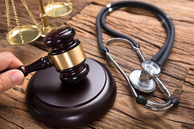 Judge's Hand Hitting Mallet By Stethoscope And Justice Scale