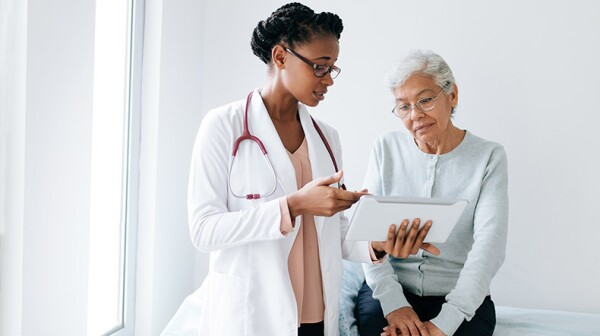 Black female doctor showing digital tablet to senior patient