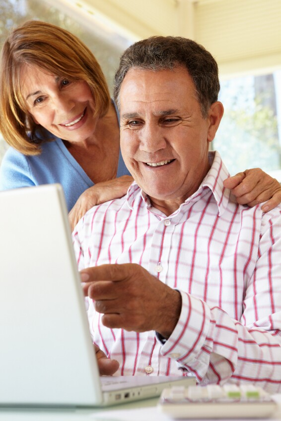 Senior Hispanic Couple Using Laptop In Home Office