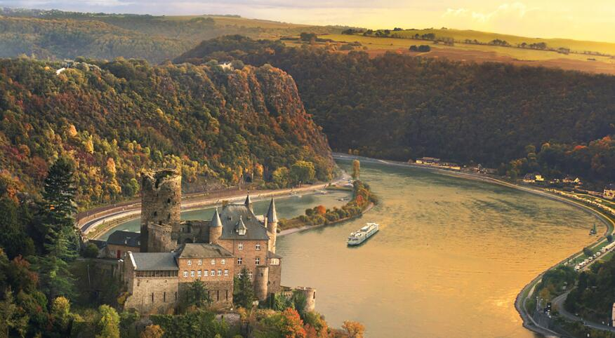 a landscape of grass cliffs, a castle and a cruise in the water