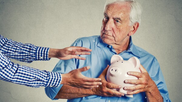 senior man grandfather holding piggy bank looking suspicious trying to protect his savings from being stolen