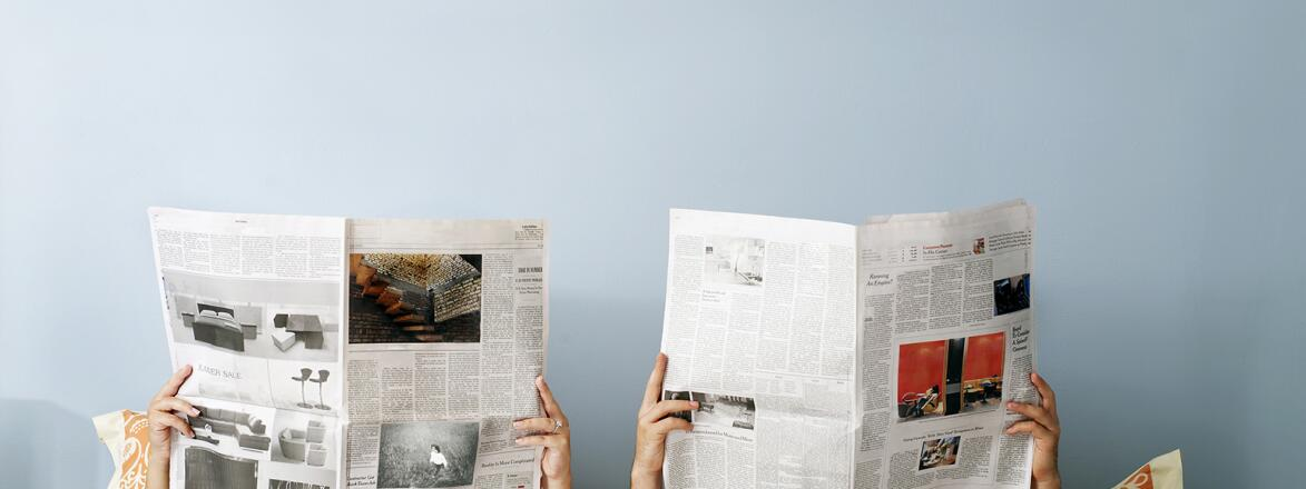 young couple laying in bed reading separate newspapers