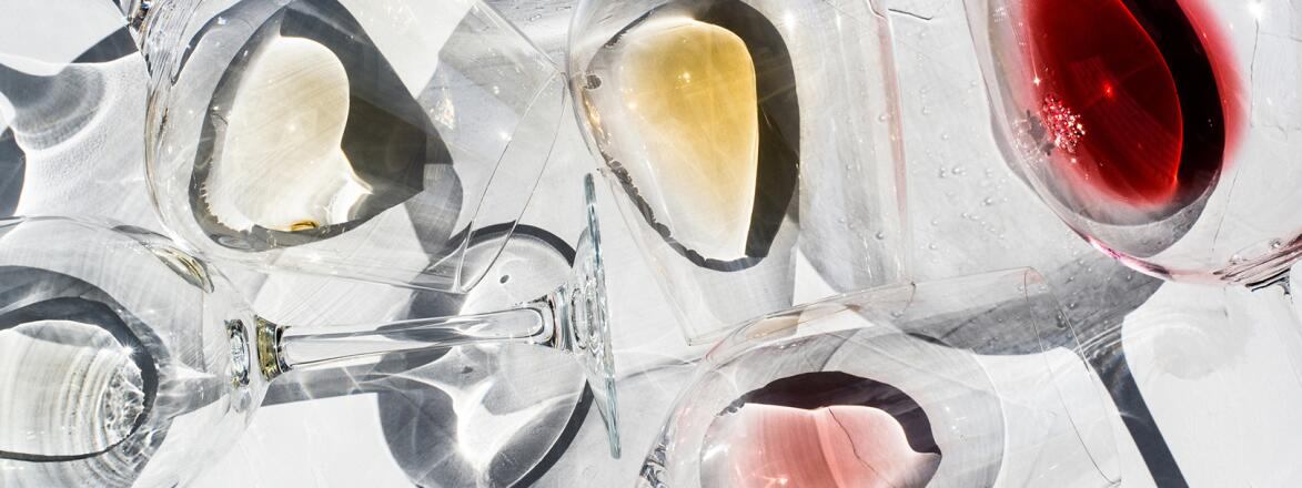 Wine Glasses on a white surface with With Different Types Of Wine inside