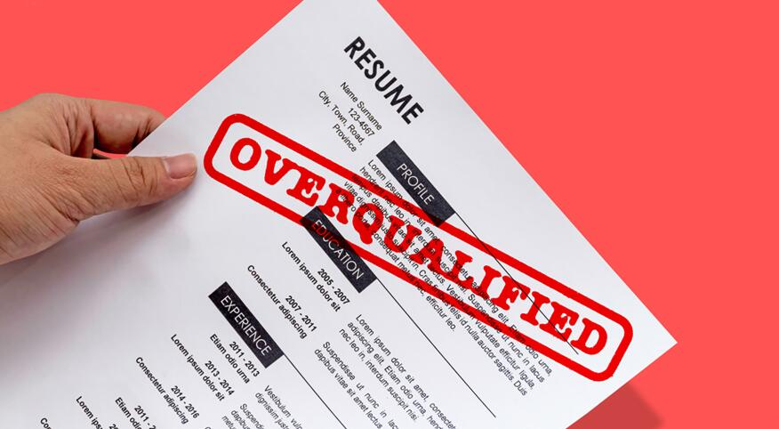 A resume on a printed out piece of paper, with a stamp in red that says OVERQUALIFIED
