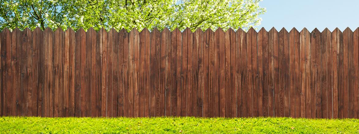 wood stained picket fence in green yard with tree behind it