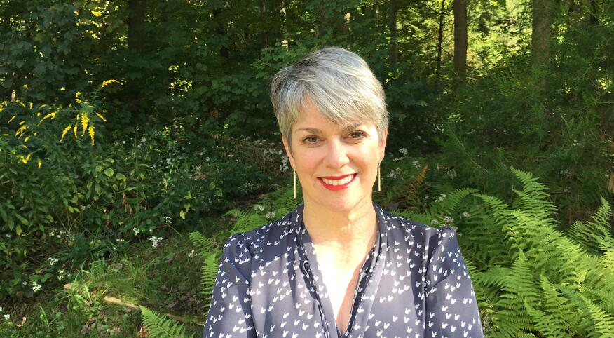 woman with a pixie haircut, grey hair smiles with her arms crossed wearing a blue long sleeve shirt in front of trees