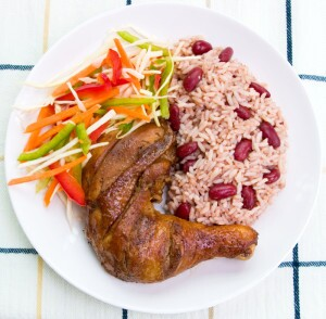 Caribbean style jerk chicken served with rice mixed with red kidney beans. Dish accompanied with vegetable salad. Shallow DOF.
