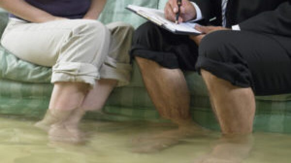 Man and woman sitting on sofa with flood water over their ankles