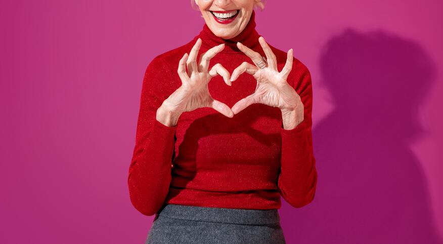 Beautiful mature woman shows heart symbol, shapes love sign with hands