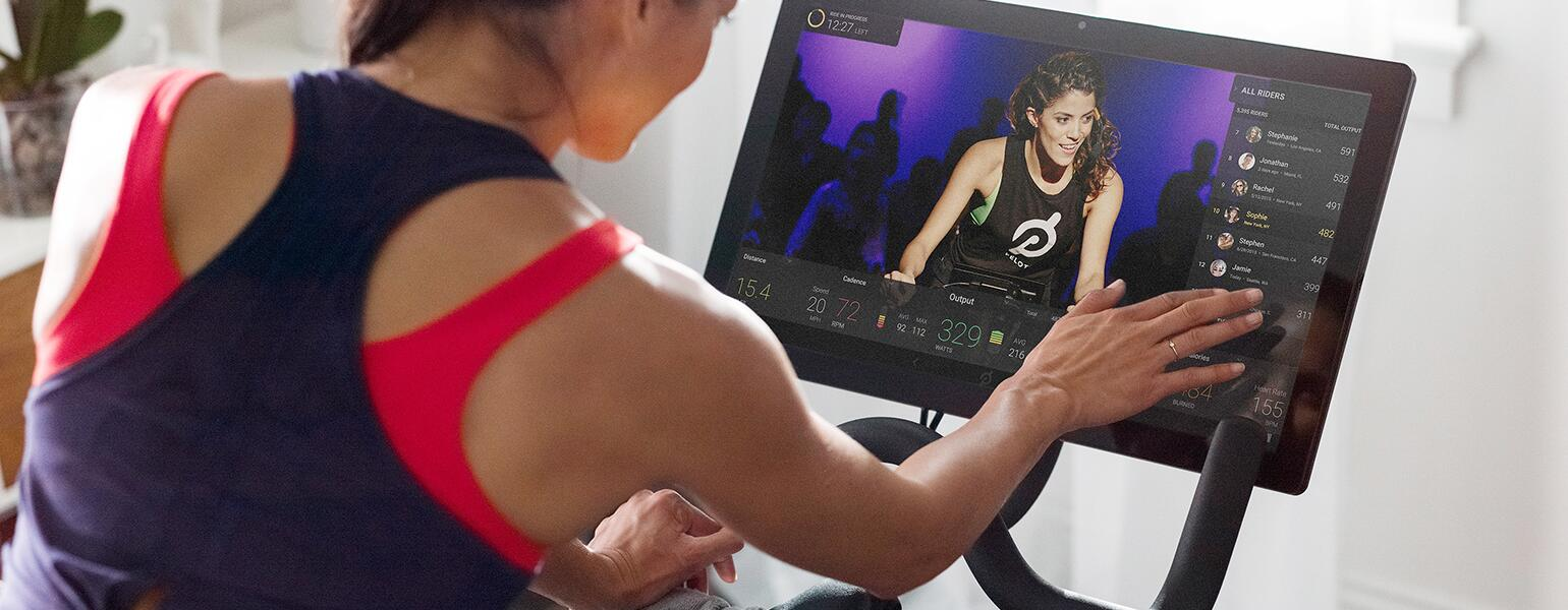 An image of a woman cycling during a Peloton class.