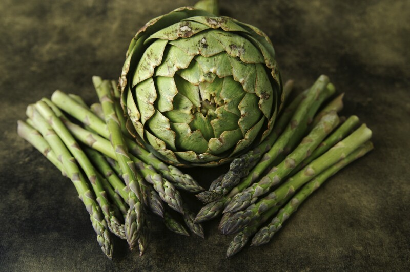 A still life of an aritchoke and asparagus on a textured background