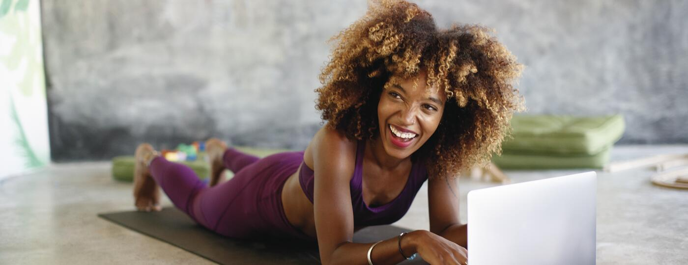 Woman on her laptop at home taking online fitness classes