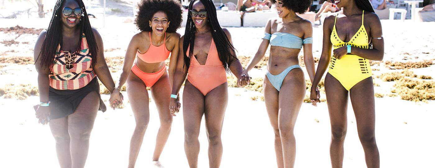 Five women in a travel group stand together smiling on an exotic getaway.