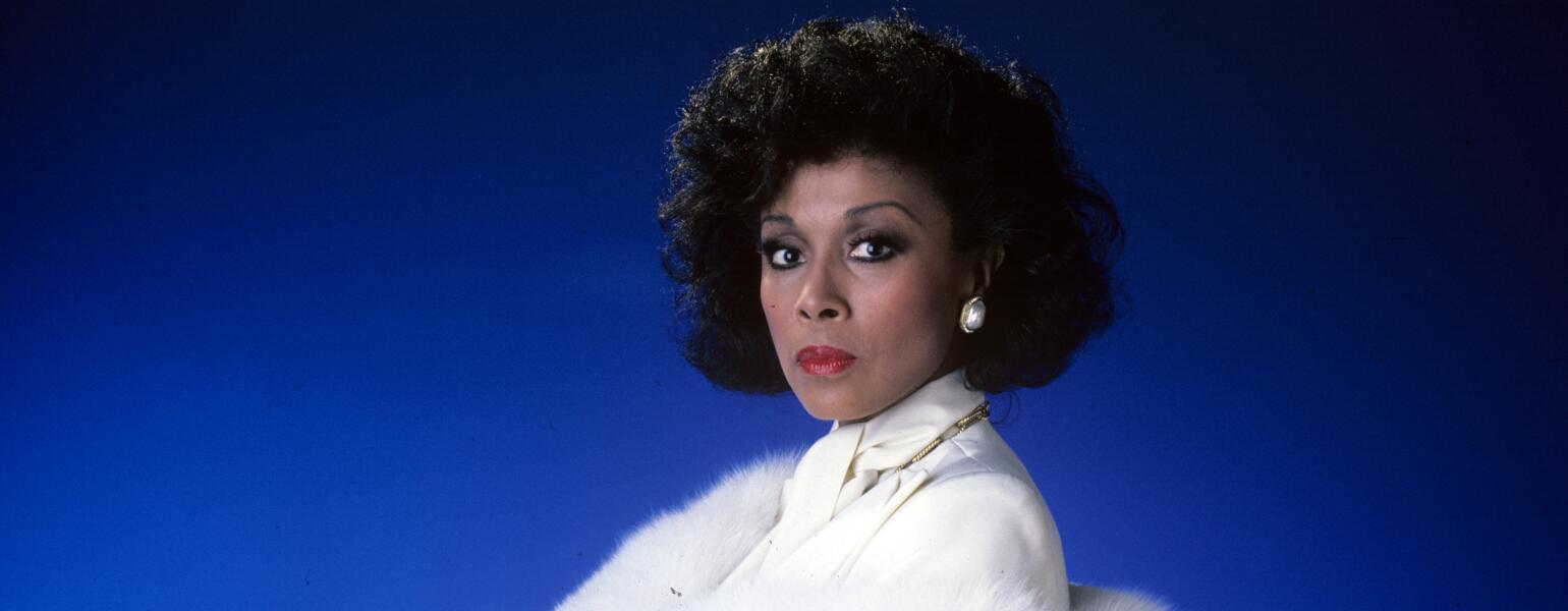 Diahann Carroll on blue background in white suit from TV show Dynasty