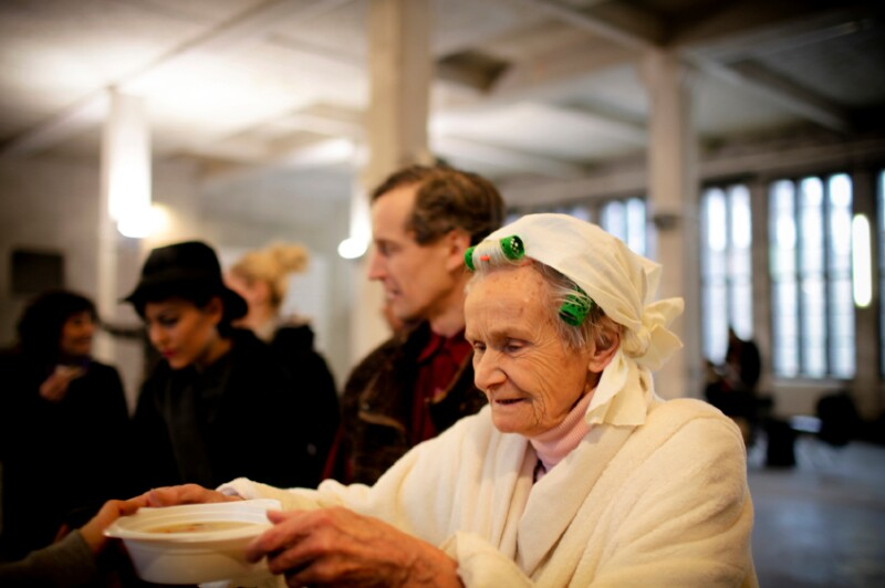 Woman eats soup at soup kitchen