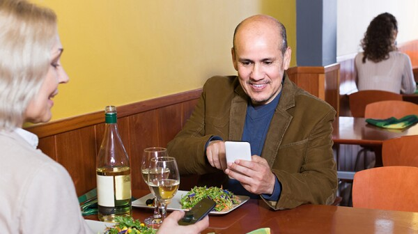 Man and woman distracted by cell phones at a restaurant