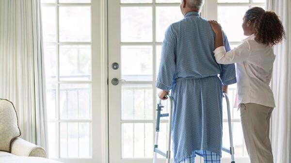 African American woman helping Senior man use walker