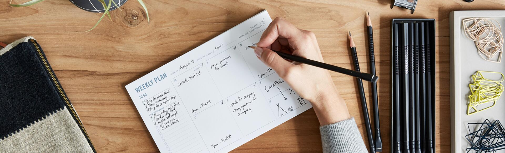 Overhead Shot Of A Small Business Owner Writing In Weekly Planner