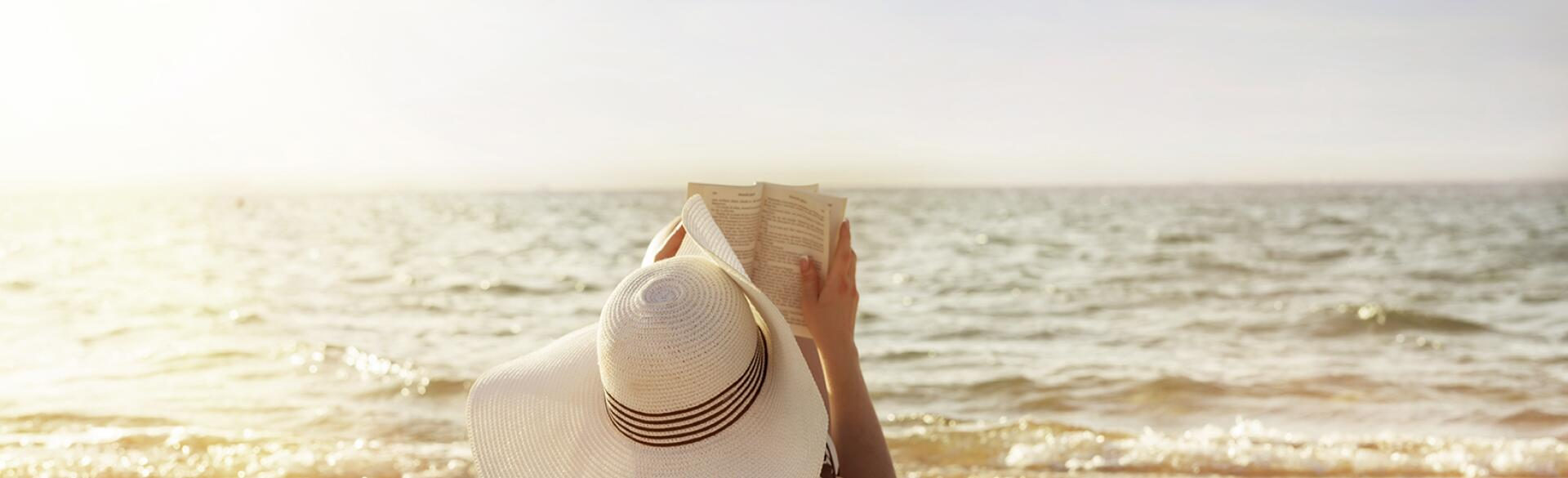 woman laying on towel reading on beach in the sun