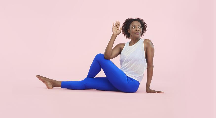 african american woman wearing athletic clothes stretching on a pink pastel background