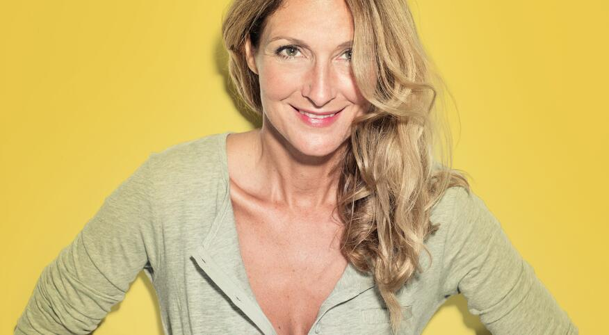 Portrait of confident blond woman in a pastel grey shirt in front of a yellow wall